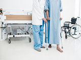 Doctor helping patient in crutches at the hospital