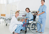 Doctors with female patient in wheelchair at hospital