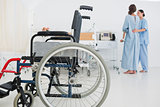 Doctor helping patient to walk with wheelchair in foreground
