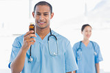 Smiling doctor holding a bottle of pills with colleague