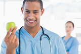 Male surgeon holding an apple with colleague behind