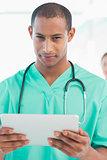 Handsome male doctor holding digital tablet