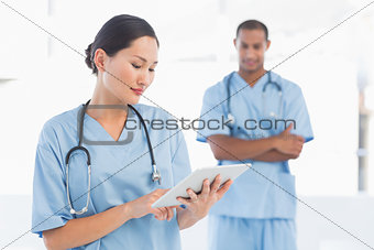 Beautiful female surgeon holding digital tablet