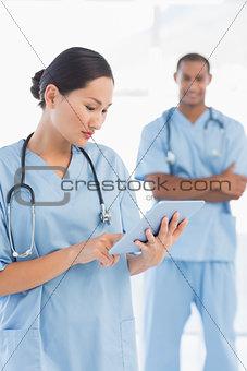 Beautiful female surgeon holding digital tablet