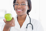 Portrait of a smiling female doctor holding an apple