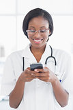 Smiling female doctor holding a mobile phone