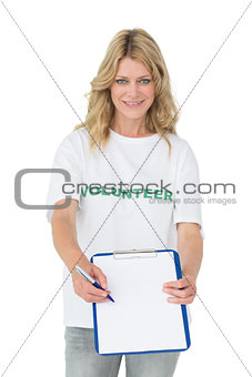 Portrait of a smiling young female volunteer holding clipboard