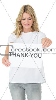 Smiling female volunteer holding thank you paper