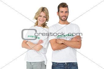 Portrait of two happy volunteers with hands crossed