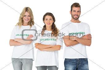 Portrait of three happy volunteers standing with hands crossed