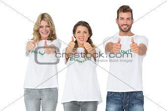 Portrait of happy three volunteers gesturing thumbs up
