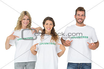 Portrait of three happy volunteers pointing to themselves