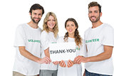 Portrait of happy volunteers holding thank you board