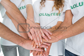 Closeup mid section of volunteers with hands together