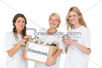 Portrait of three smiling young women with donation box