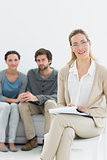 Female financial adviser with young couple in background