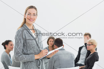 Portrait of therapist with group therapy in session in background