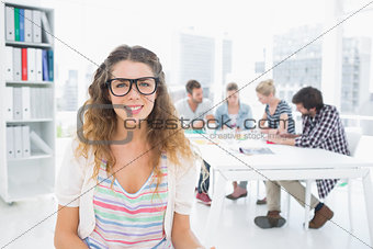 Casual female artist with colleagues in the background