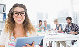 Smiling woman using digital tablet with colleagues in background at office