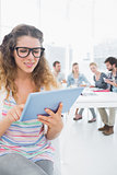 Woman using digital tablet with colleagues in background