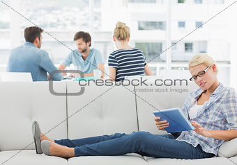 Woman using digital tablet with colleagues in background at creative office