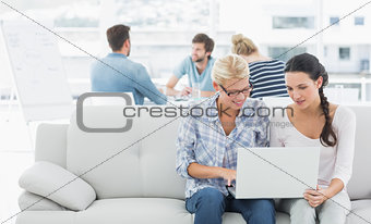 Women using laptop with colleagues in background at creative office
