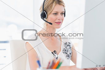Casual woman with headset using computer