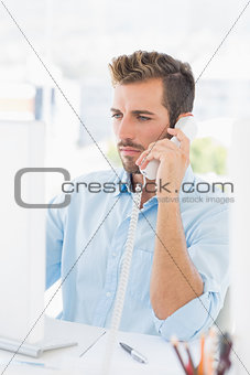 Serious man using phone and computer in office