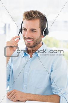 Closeup of a casual young man with headset using computer