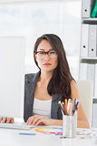 Serious young woman using computer in office