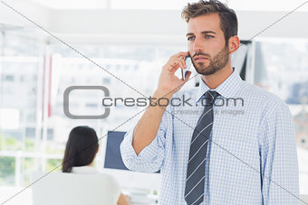 Casual male artist using mobile phone with colleague in the background