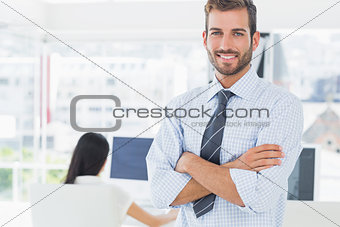 Portrait of a casual male artist with colleague in background
