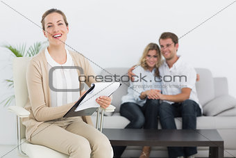Financial adviser writing notes with couple in background