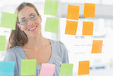 Female artist looking at colorful sticky notes