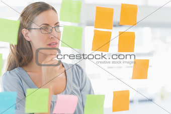 Concentrated artist looking at colorful sticky notes