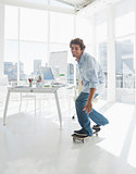 Happy man skateboarding in a bright office