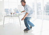 Happy young man skateboarding in office