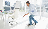 Happy young man skateboarding in a bright office