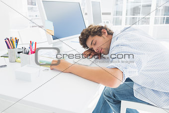 Casual businessman with head over keyboard in the office