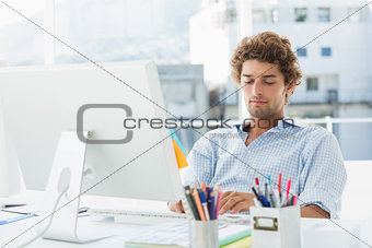 Casual young man using computer in bright office