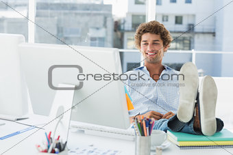 Casual young man with legs on desk in bright office