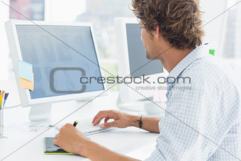 artist drawing something on graphic tablet with pen