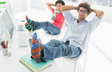 Relaxed casual couple with legs on desk in office