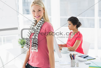 Casual business woman with colleague using computer