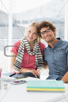 Casual business couple sitting in a bright office