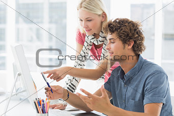 Casual couple using computer in bright office