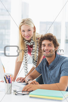 Casual business couple using computer in bright office