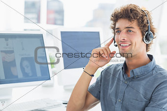 Smiling casual young man with headset in office