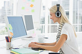 Casual young woman with headset using computer in office