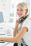 Portrait of of a woman with headset sitting in office